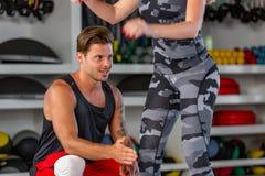 Глубокое сидение на корточках Пары фитнеса в sportswear делая низкие тренировки на спортзале, Стоковое Изображение RF