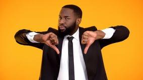 Глубоко неудовлетворенный чернокожий человек показывая двойные большие пальцы руки-вниз, качественный сервис низкого качества стоковое фото