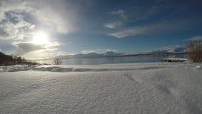 Глубоко открытый ландшафт фьорда с могущественной снежной горной цепью на заднем плане сток-видео