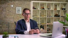 Глубоко сфокусированный кавказский бизнесмен перечисляет его smartphone пока сидящ на белом столе в офисе кирпича самостоятельно акции видеоматериалы