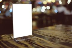 Глумитесь вверх по рамке меню стоя на деревянной таблице в кафе бар-ресторана стоковая фотография rf