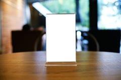 Глумитесь вверх по рамке меню стоя на деревянной таблице в кафе бар-ресторана стоковые фото