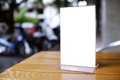 Глумитесь вверх по рамке меню стоя на деревянной таблице в кафе бар-ресторана стоковое изображение