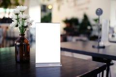 Глумитесь вверх по рамке меню стоя на деревянной таблице в кафе бар-ресторана Стоковая Фотография