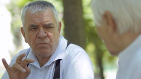 Глухой-безгласный старший человек разговаривая с руками с глухой-безгласной женой в парке акции видеоматериалы