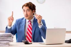 Глухой работник используя слуховой аппарат в офисе стоковое изображение rf
