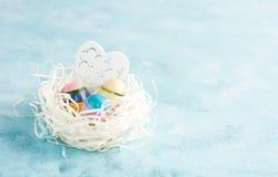 Гнездо белой бумаги с 3 винтажными пасхальными яйцами и деревянным сердцем на голубой предпосылке Стоковое Изображение