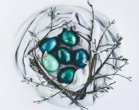 Гнездо ткани с пасхальными яйцами в бирюзе и золоте украшенных с вербой pussy на белизне стоковое фото rf