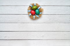 Гнездитесь покрашенный венок яичек на белой деревянной предпосылке планок восточно Стоковое Изображение