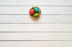 Гнездитесь покрашенный венок яичек на белой деревянной предпосылке планок Стоковое фото RF