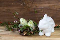 Гнездитесь с пасхальными яйцами и керамической коробкой кролика на деревянной предпосылке Стоковое Изображение RF