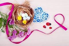 Гнездитесь с яичками и цыпленоками на деревянной предпосылке Пасха Стоковое Изображение RF