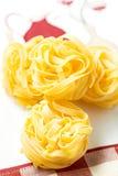 Гнезди сухого tagliatelle макаронных изделий на вертикали и красном цвете скатерти Стоковое фото RF