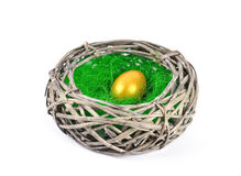 Гнездй с золотистым пасхальным яйцом Стоковое Фото