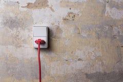 Гнездо с красным проводом на grungy стене Стоковое Изображение