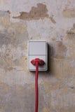 Гнездо с красным проводом на grungy стене Стоковое Фото