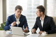 Говорить 2 бизнесменов, сидя на столе офиса с coff компьтер-книжки Стоковые Изображения RF