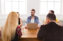 говорить встречи компьтер-книжки стола cmputer бизнесмена дела сь к использованию женщины Молодая команда в современном офисе Стоковое Изображение