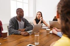 говорить встречи компьтер-книжки стола cmputer бизнесмена дела сь к использованию женщины Молодая команда в современном офисе Стоковое Изображение RF