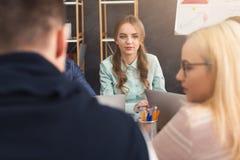 говорить встречи компьтер-книжки стола cmputer бизнесмена дела сь к использованию женщины Молодая команда в современном офисе Стоковое Фото