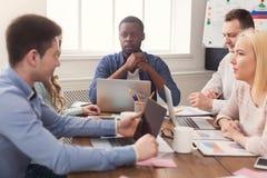 говорить встречи компьтер-книжки стола cmputer бизнесмена дела сь к использованию женщины Многонациональная команда в офисе Стоковые Изображения