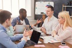 говорить встречи компьтер-книжки стола cmputer бизнесмена дела сь к использованию женщины Многонациональная команда в офисе Стоковые Изображения RF