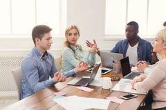 говорить встречи компьтер-книжки стола cmputer бизнесмена дела сь к использованию женщины Многонациональная команда в офисе Стоковая Фотография RF