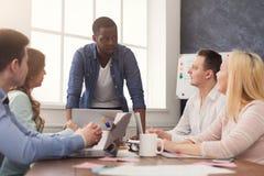 говорить встречи компьтер-книжки стола cmputer бизнесмена дела сь к использованию женщины Многонациональная команда в офисе Стоковое Изображение RF