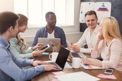 говорить встречи компьтер-книжки стола cmputer бизнесмена дела сь к использованию женщины Многонациональная команда в офисе Стоковая Фотография