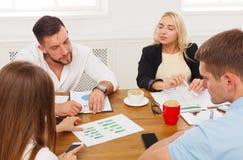 говорить встречи компьтер-книжки стола cmputer бизнесмена дела сь к использованию женщины Молодые бизнесмены и женщины битников н Стоковая Фотография