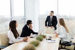 говорить встречи компьтер-книжки стола cmputer бизнесмена дела сь к использованию женщины Бизнесмены в formalwear обсуждая что-то Стоковые Изображения