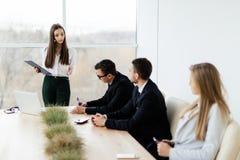говорить встречи компьтер-книжки стола cmputer бизнесмена дела сь к использованию женщины Бизнес-леди дает извещение для команды  Стоковые Изображения