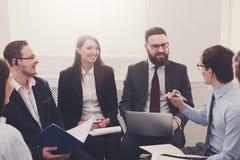 говорить встречи компьтер-книжки стола cmputer бизнесмена дела сь к использованию женщины Молодые бизнесмены и женщины на совреме Стоковое Фото
