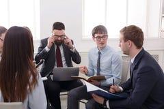 говорить встречи компьтер-книжки стола cmputer бизнесмена дела сь к использованию женщины Молодые бизнесмены и женщины на совреме Стоковое Изображение