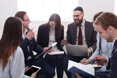 говорить встречи компьтер-книжки стола cmputer бизнесмена дела сь к использованию женщины Молодые бизнесмены и женщины на совреме Стоковые Фото