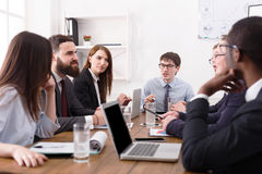 говорить встречи компьтер-книжки стола cmputer бизнесмена дела сь к использованию женщины Молодые бизнесмены в офисе Стоковые Фото