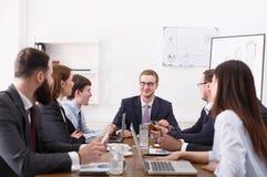 говорить встречи компьтер-книжки стола cmputer бизнесмена дела сь к использованию женщины Молодая команда в современном офисе Стоковая Фотография RF