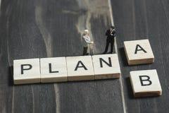 Говорить дела миниатюрный около выбирает план a или b стоковая фотография rf