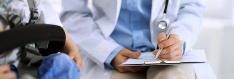 Говорить доктора и пациента Врач на работе в больнице пока пишущ вверх по историческим рекордам лекарства формирует на доске сзаж стоковая фотография