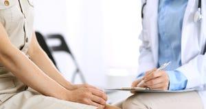 Говорить доктора и пациента Врач на работе в больнице пока пишущ вверх по историческим рекордам лекарства формирует на доске сзаж стоковые изображения rf