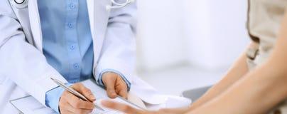 Говорить доктора и пациента Врач на работе в больнице пока пишущ вверх по историческим рекордам лекарства формирует на доске сзаж стоковая фотография rf
