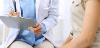 Говорить доктора и пациента Врач на работе в больнице пока пишущ вверх по историческим рекордам лекарства формирует на доске сзаж стоковое изображение