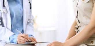 Говорить доктора и пациента Врач на работе в больнице пока пишущ вверх по историческим рекордам лекарства формирует на доске сзаж стоковое изображение rf