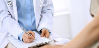 Говорить доктора и пациента Врач на работе в больнице пока пишущ вверх по историческим рекордам лекарства формирует на доске сзаж стоковые изображения