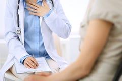 Говорить доктора и пациента Врач на работе в больнице пока пишущ вверх по историческим рекордам лекарства формирует на доске сзаж стоковое фото rf