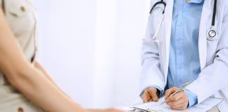 Говорить доктора и пациента Врач на работе в больнице пока пишущ вверх по историческим рекордам лекарства формирует на доске сзаж стоковые фотографии rf