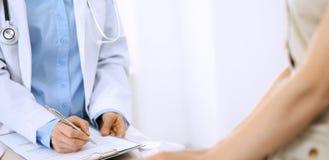 Говорить доктора и пациента Врач на работе в больнице пока пишущ вверх по историческим рекордам лекарства формирует на доске сзаж стоковые фото