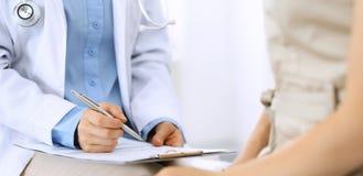 Говорить доктора и пациента Врач на работе в больнице пока пишущ вверх по историческим рекордам лекарства формирует на доске сзаж стоковое фото