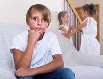 2 говорить девушек и sulky мальчик сидя отдельно дома Стоковые Фотографии RF