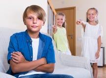 2 говорить девушек и sulky мальчик сидя отдельно дома Стоковые Изображения